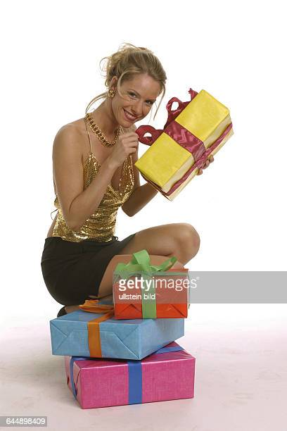 Junge Frau in Party-Kleidung mit mehreren Geschenkkartons, young woman clad in a party dress with some gift boxes