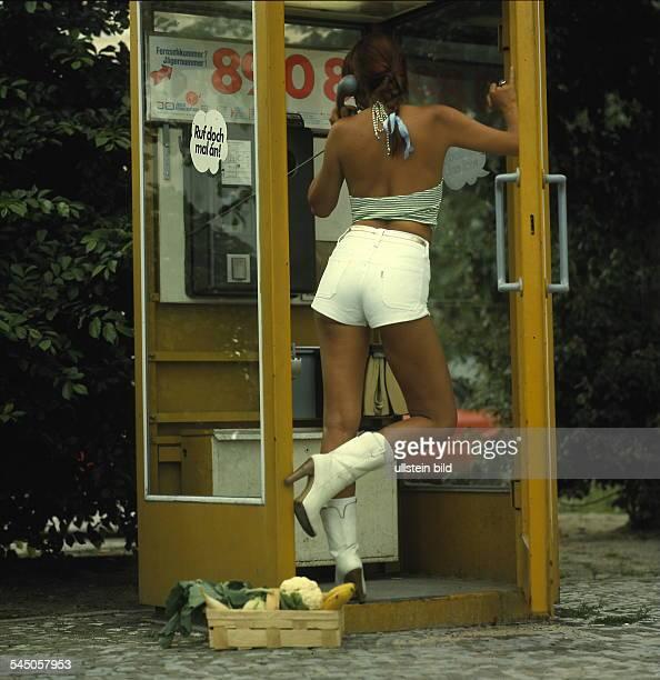 Junge Frau mit hot pants telefoniert in einer Telefonzelle Berlin West 70er Jahre