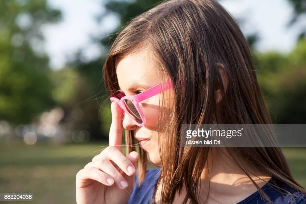 Junge Frau mit pinker Sonnenbrille