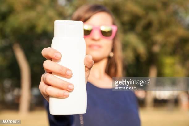 Junge Frau mit Sonnenbrille hält Sonncreme Tube