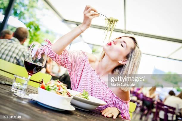 junge frau schlürft spaghetti in gastgarten - essen germany stock pictures, royalty-free photos & images