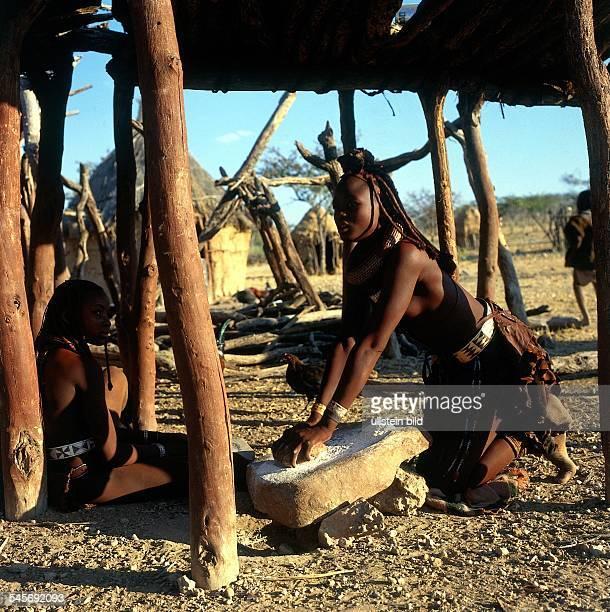 Junge Himba Frau in ihrem Dorf inOpuwo beim Mahlen von Kornin traditioneller Weise 1995 col