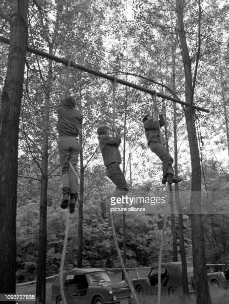 Junge Leute klettern an einem Seil bei der Bestenermitttlung in der vormilitärischen Ausbildung im Jahre 1977 in der Gegend von Hettstedt. Auf dem...