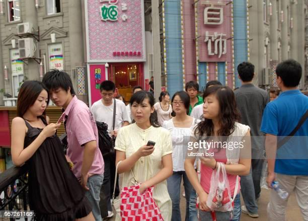 Junge Leute mit Handys auf einer Fußgängerbrücke im Zentrum der Altstadt von Wuhan aufgenommen am Wuhan ist Hauptstadt der Provinz Hubei Rund 5200000...