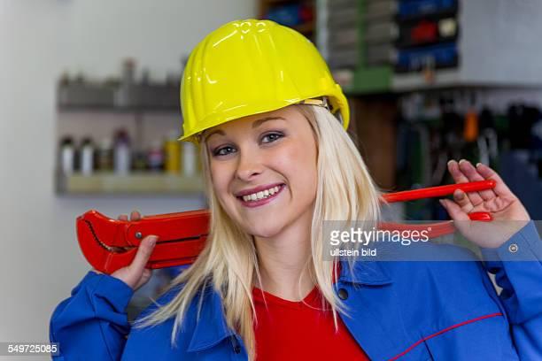 Junge Mechanikerin mit gelben Helm und Schraubenschlüssel in einer Werkstatt Seltene Frauenberufe