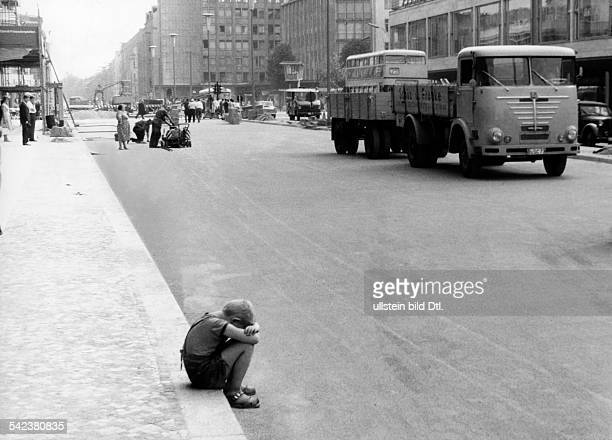 Junge sitzt verloren auf der Bordsteinkante 1962