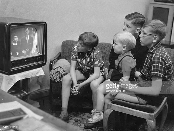 Jungen auf Sofa und Hocker sehen sich gemeinsam eine Sendung im Fernsehen an1959