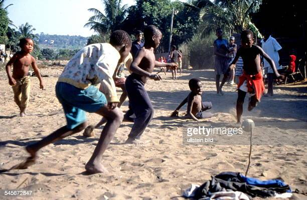 Jungen spielen Fussball auf sandigemBoden in einem Vorort von Maputo 1998