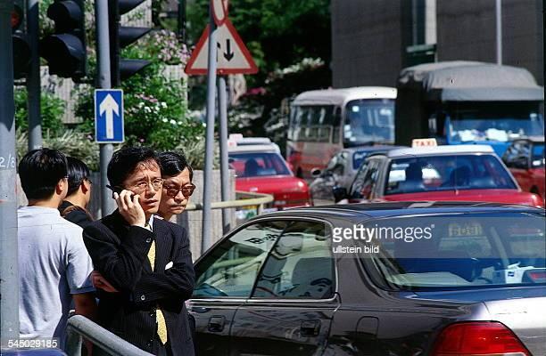 Junger Geschäftsmann mit Handy imStraßenverkehr 041997 col