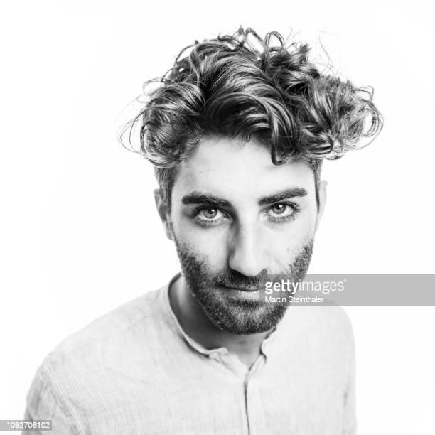 junger mann mit bart und locken schaut direkt in kamera - stoppelbart stock-fotos und bilder
