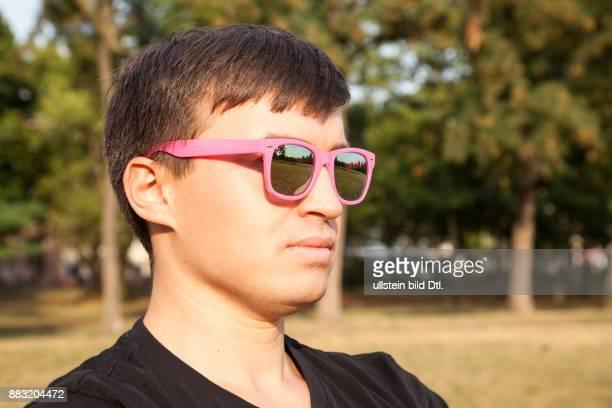 Junger Mann mit pinker Sonnenbrille