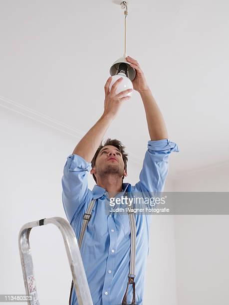 Junger Mann schraubt neue Glhbirne an