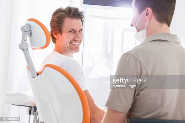 Junger Mann während der Behandlung beim Zahnarzt