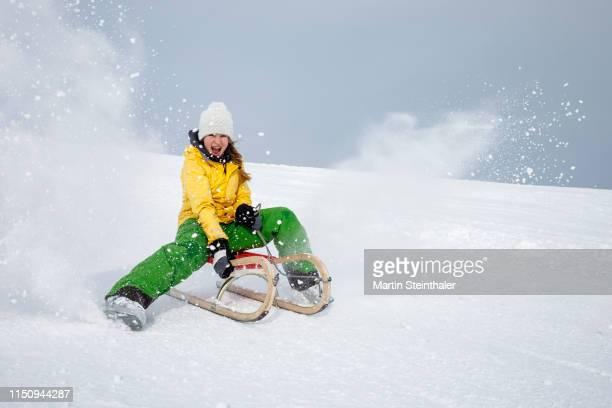 junges mädchen auf schlitten rodelt im schnee - schlitten stock-fotos und bilder