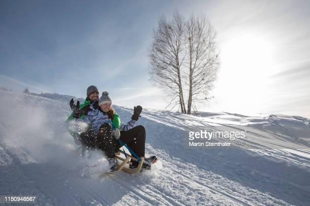 junges mädchen auf schlitten rodelt im schnee - 橇 ストックフォトと画像