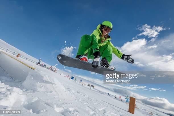 junges mädchen mit snowboard springt über rampe - snowboarding stock pictures, royalty-free photos & images
