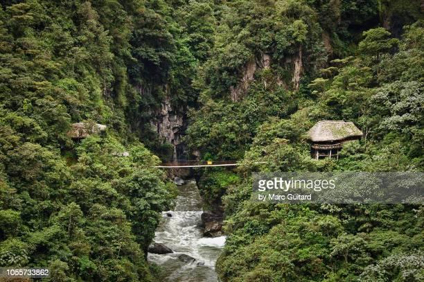 jungle hut and bridge over roaring river, baños, ecuador - las américas fotografías e imágenes de stock