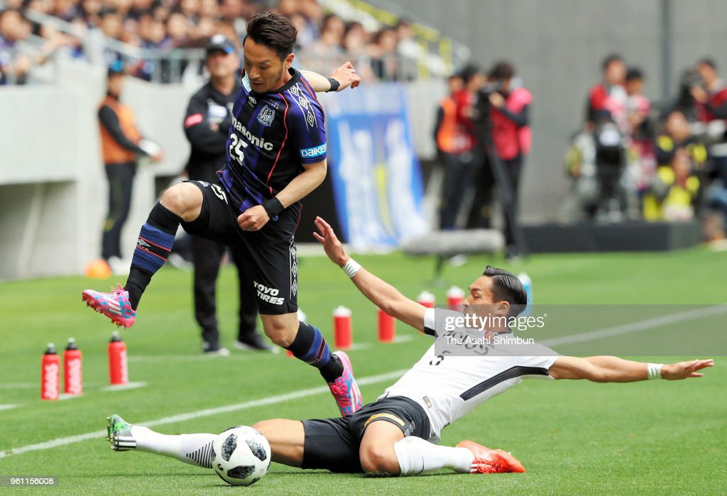 Jungo Fujimoto of Gamba Osaka is tackled by Tomoaki Makino of Urawa Red Diamodns during the J.League J1 match between Gamba Osaka and Urawa Red Diamonds at Panasonic Stadium Suita on May 19, 2018 in Suita, Osaka, Japan.