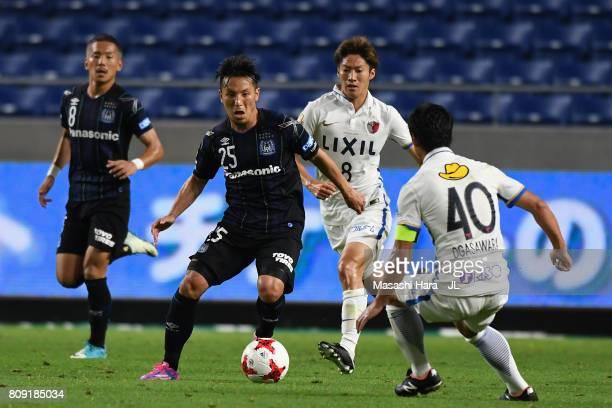 Jungo Fujimoto of Gamba Osaka takes on Mitsuo Ogasawara of Kashima Antlers during the JLeague J1 match between Gamba Osaka and Kashima Antlers at...