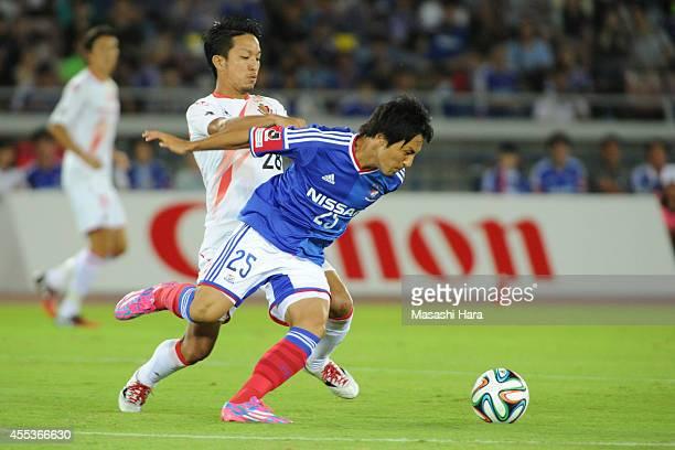 Jungo Fujimoto of Yokohama F.Marinos and Taishi Taguchi of Nagoya Grampus compete for the ball during the J.League match between Yokohama F.Marinos...