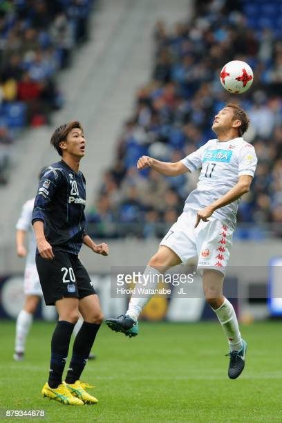 Junichi Inamoto of Consadole Sapporo and Shun Nagasawa of Gamba Osaka compete for the ball during the JLeague J1 match between Gamba Osaka and...