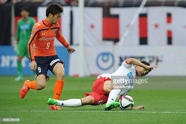 Junichi Inamoto of Consadole Sapporo and Takamitsu Tomiyama of Omiya Ardija compete for the ball during the JLeague second division match between...