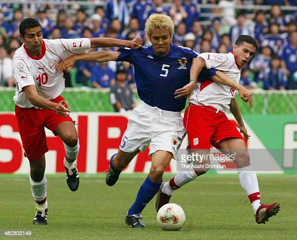 Junichi Inamoto of Japan competes for the ball against Kais Ghodhbane and Slim Benachour of Tunisia during the FIFA World Cup Korea/Japan Group H...