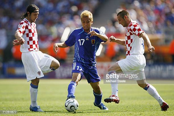 Junichi Inamoto of Japan is challenged by Niko Kovac and Robert Kovac of Croatia during the FIFA World Cup Germany 2006 Group F match between Japan...