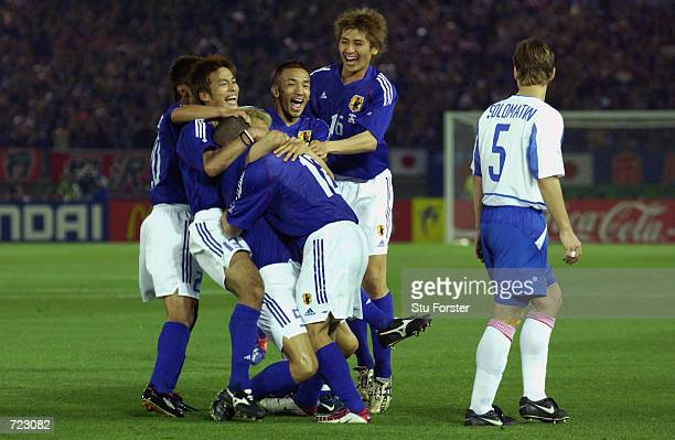 Junichi Inamoto of Japan is mobbed after scoring the winning goal during the FIFA World Cup Finals 2002 Group H match between Japan and Russia played...