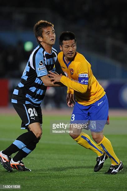 Junichi Inamoto of Kawasaki Frontale and Atsushi Yanagisawa of Vegalta Sendai compete during the JLeague Yamazaki Nabisco Cup Group A match between...