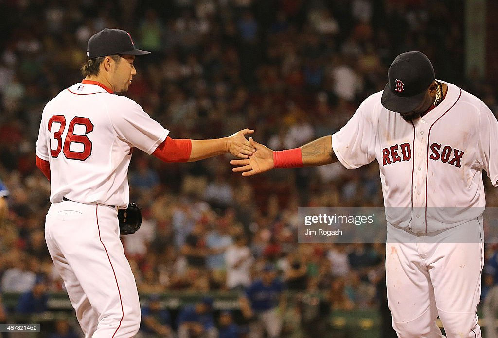 Junichi Tazawa #36 of the Boston Red Sox celebrates with Pablo Sandoval after a scoreless inning against the Toronto Blue Jay at Fenway Park on September 8, 2015 in Boston, Massachusetts.