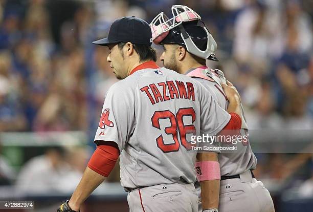 Junichi Tazawa of the Boston Red Sox is congratulated by Sandy Leon after pitching a scoreless eighth inning during MLB game action against the...