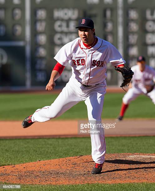 Junichi Tazawa of the Boston Red Sox pitches during the eighth inning against the Seattle Mariners at Fenway Park on August 24 2014 in Boston...