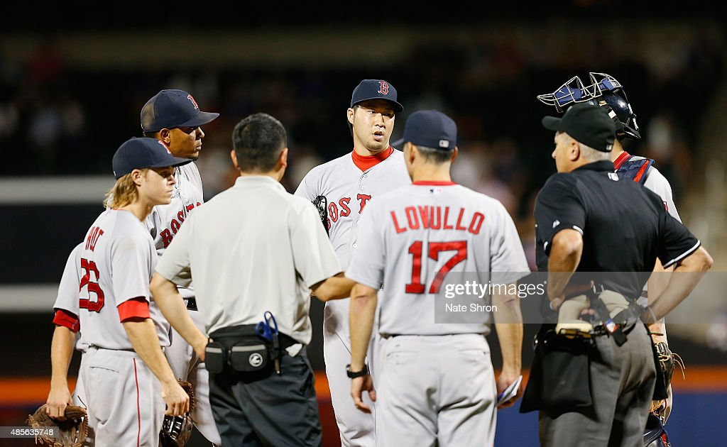 Junichi Tazawa #36 of the Boston Red Sox talks with teammates and interim mangaer Torey Lovullo #17 in between pitches in the tenth inning against the New York Mets on August 28, 2015 at Citi Field in the Flushing Neighborhood of the Queens borough of New York City.