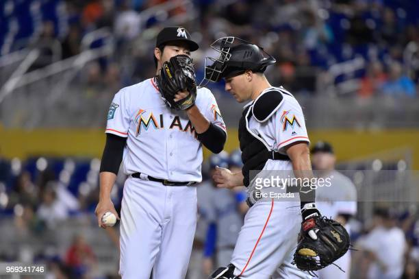 Junichi Tazawa of the Miami Marlins talks to catcher JT Realmuto during the sixth inning against the Los Angeles Dodgers at Marlins Park on May 16...