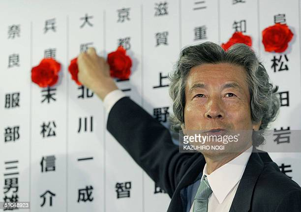 Junichiro Koizumi Japanese Prime Minister and President of the ruling Liberal Democratic Party puts a rosette on the name of an elected his party...