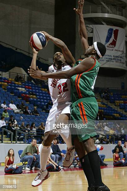 Junie Sanders of the Fayetteville Patriots drives against Hiram Fuller of the Charleston Lowgators at the Crown Coliseum November 29 2003 in North...