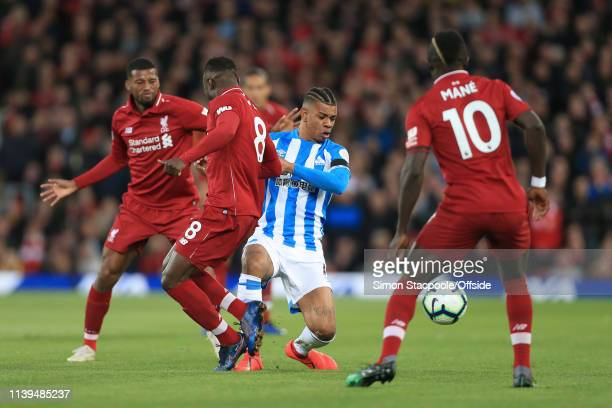 Juninho Bacuna of Huddersfield is outnumbered during the Premier League match between Liverpool and Huddersfield Town at Anfield on April 26 2019 in...