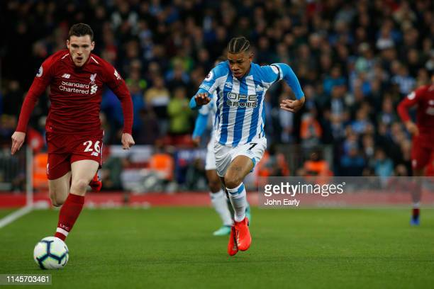 Juninho Bacuna of Huddersfield Town and Andy Robertson of Liverpool race for the ball during the Premier League match between Liverpool FC and...