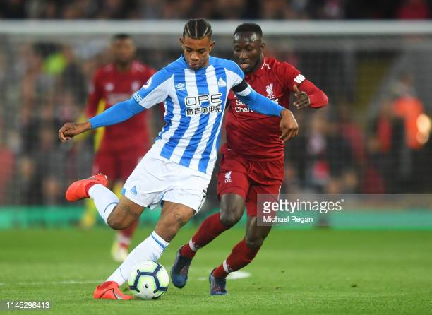Juninho Bacuna of Huddersfield Town holds off Naby Keita of Liverpool during the Premier League match between Liverpool FC and Huddersfield Town at...