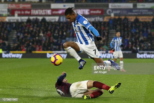 Juninho Bacuna of Huddersfield Town jumps over a tackle from Javier Manquillo of Newcastle United during the Premier League match between...