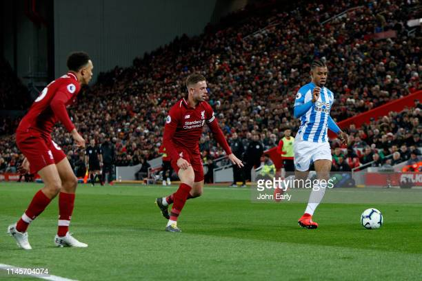 Juninho Bacuna of Huddersfield Town looks to run clear of Jordan Henderson and Trent AlexanderArnold of Liverpool during the Premier League match...