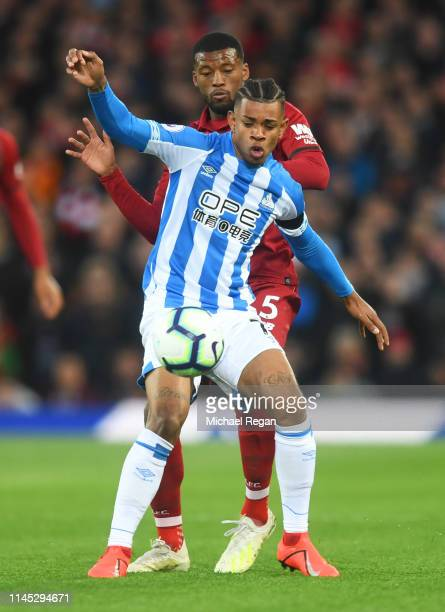 Juninho Bacuna of Huddersfield Town shields the ball from Georginio Wijnaldum of Liverpool during the Premier League match between Liverpool FC and...