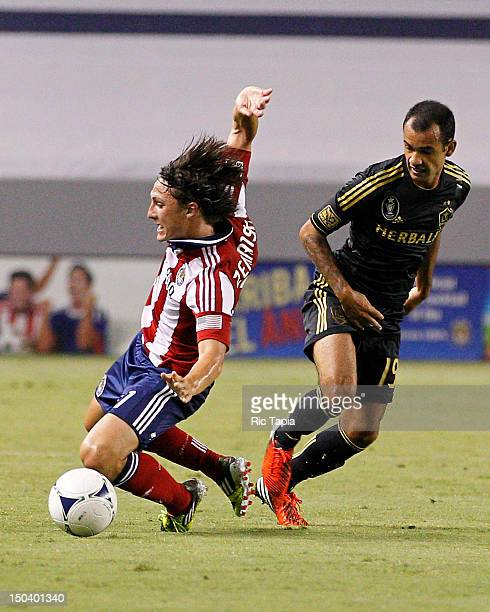 Juninho of Los Angeles Galaxy trips Jose Erick Correa of Chivas USA during the MLS match against at The Home Depot Center on August 12 2012 in Carson...