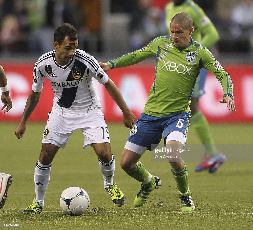 Juninho #19 of the Los Angeles Galaxy dribbles against Osvaldo Alonso #6 of the Seattle Sounders at CenturyLink Field on May 2, 2012 in Seattle, Washington. The Sounders defeated the Galaxy 2-0.