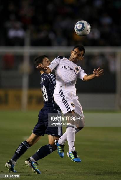 Juninho of the Los Angeles Galaxy heads the ball away from Milos Stojcev of Sporting Kansas City at The Home Depot Center on May 14 2011 in Carson...