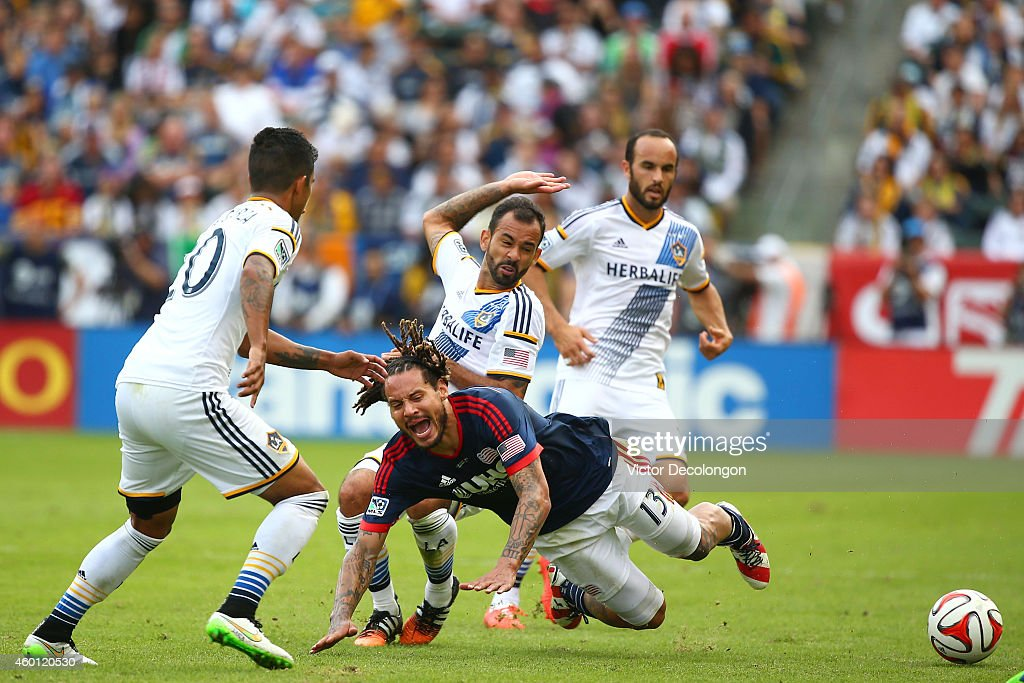 Juninho #19 of the Los Angeles Galaxy tackles Jermaine Jones #13 of the New England Revolution in the second half during 2014 MLS Cup at StubHub Center on December 7, 2014 in Los Angeles, California. The Galaxy defeated the Revolution 2-1.