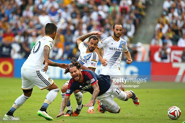 Juninho of the Los Angeles Galaxy tackles Jermaine Jones of the New England Revolution in the second half during 2014 MLS Cup at StubHub Center on...