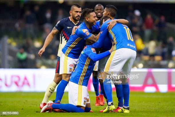Juninho of Tigres celebrates with teammates after scoring the first goal of his team during the semifinal first leg match between America and Tigres...