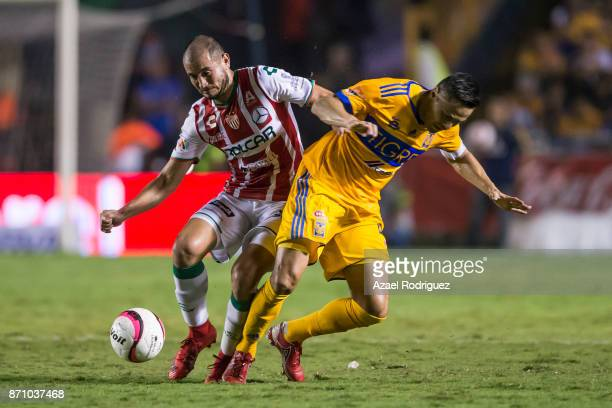 Juninho of Tigres fights for the ball with Carlos Gonzalez of Necaxa during the 16th round match between Tigres UANL and Necaxa as part of the Torneo...